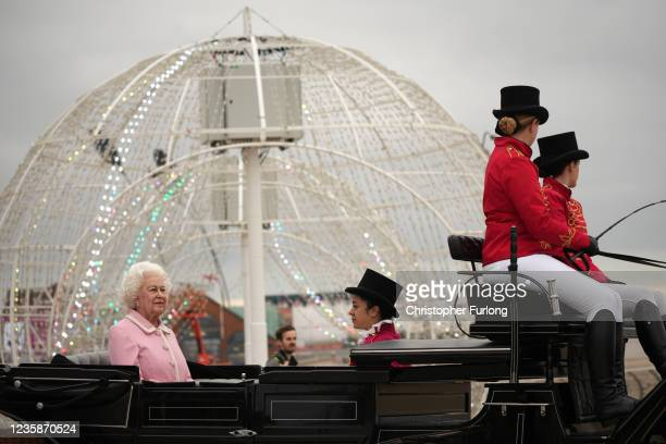 Waxwork of Queen Elizabeth II is escorted in a horse and carriage along the promenade as it makes it's way to Madame Tussauds on October 14, 2021 in...