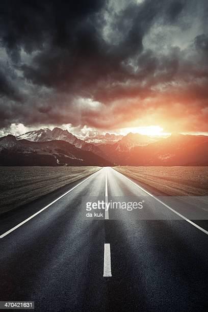 Weg.  Leeren Straße in die Berge im Sonnenuntergang.