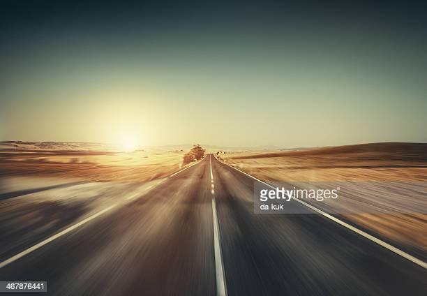 Forma de avanzar en movimiento.  Vacía carretera al atardecer.