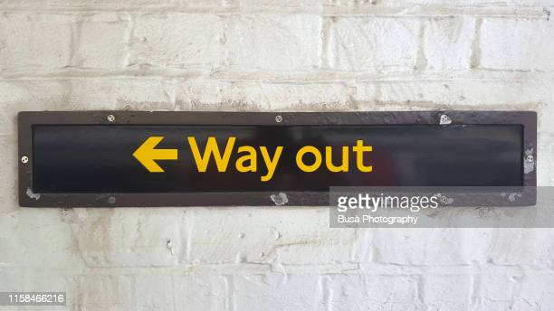 """""""way out"""" sign on brick wall in london subway - political party stock pictures, royalty-free photos & images"""