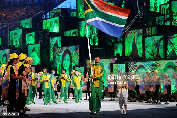 Wayde Van Niekerk of South Africa carries his country's flag during the Opening Ceremony of the Rio 2016 Olympic Games at Maracana Stadium on August...