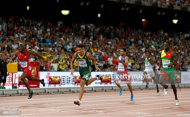 Wayde Van Niekerk of South Africa crosses the finish line to win gold ahead of Lashawn Merritt of the United States and Kirani James of Grenada in...
