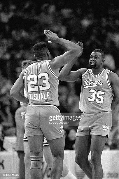Wayman Tisdale and Antoine Carr of the Sacramento Kings high five each other against the Chicago Bulls on March 24 1990 at the United Center in...