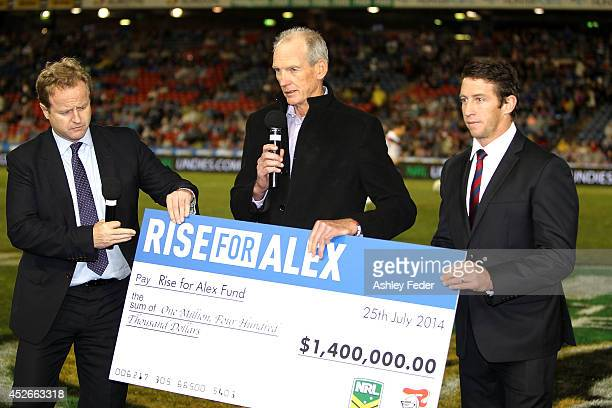 Wayne Bennett receives a cheque for Alex McKinnon from the Rise for Alex round during the round 20 NRL match between the Newcastle Knights and the...