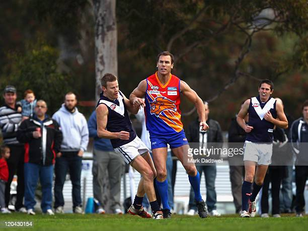 Wayne Carey playing for the Maribyrnong Lions gives a hip and shoulder to Paul Harris of the Heights during the Essendon Distrct Football League AFL...