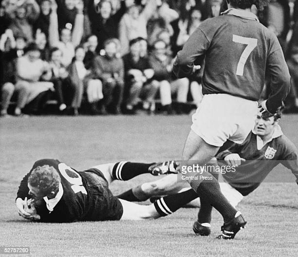 Wayne Cottrell of the New Zealand All Blacks dives past Mike Gibson and John Taylor to score the first try in the 4th test match against the British...