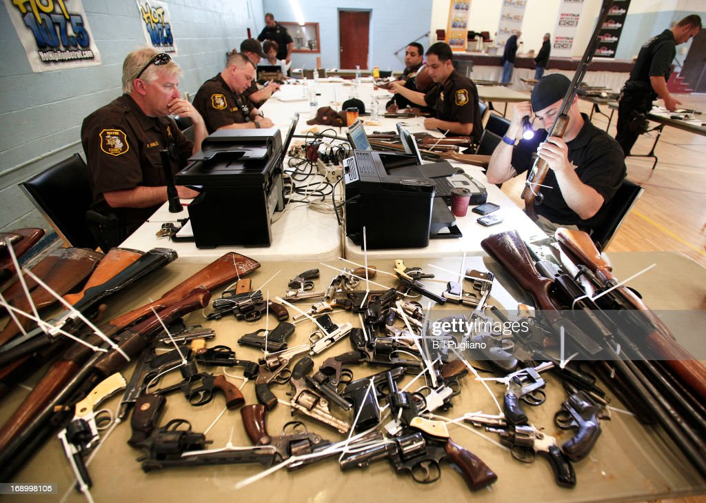 Wayne County Sheriff's officers examine and enter into a database guns people brought in to exchange for a $50 Meijer gift card at a 'Groceries For Guns' gun buyback program May 18, 2013 at the New St. Paul Tabernacle Church of God in Christ in Detroit, Michigan. The event was sponsored by the law firm Goodman Acker P.C. in a public-private partnership with Wayne County.