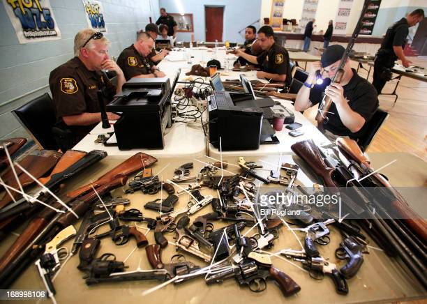 Wayne County Sheriff's officers examine and enter into a database guns people brought in to exchange for a $50 Meijer gift card at a 'Groceries For...