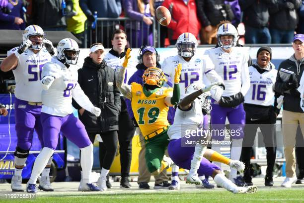 Wayne Davis of the James Madison Dukes knocks the ball away from Jimmy Kepouros of the North Dakota State Bison during the Division I FCS Football...