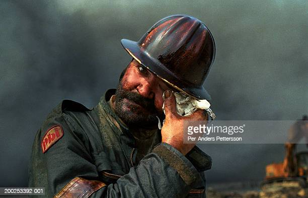 Wayne de Champs, a fire fighter from Calgary, Canada cleanse his face after working with burning wells on August 13, 1991. He worked at Greater...
