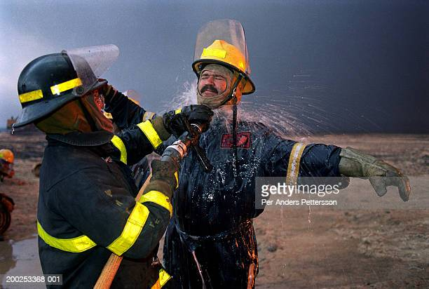 Wayne de Champs, a fire fighter from Calgary, Canada cools off after putting out oil fires on August 13, 1991. He worked at Greater Burhan oilfield...