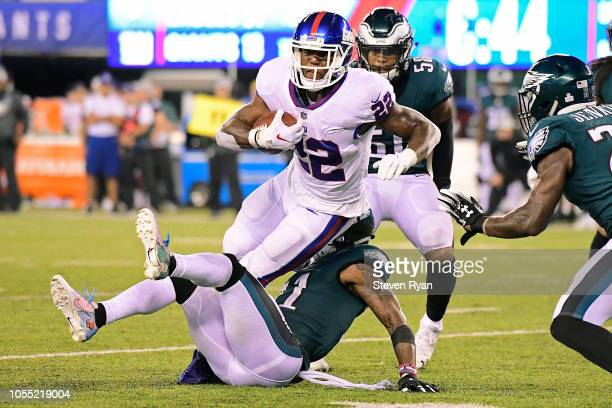 Wayne Gallman of the New York Giants gets tripped up by Jalen Mills of the Philadelphia Eagles at MetLife Stadium on October 11 2018 in East...