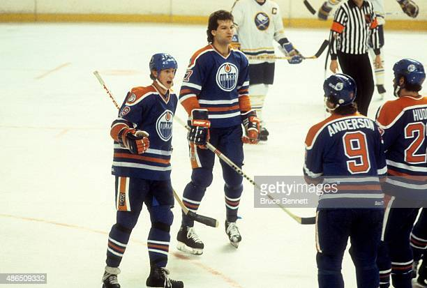 Wayne Gretzky and Dave Semenko of the Edmonton Oilers celebrate with teammates Glenn Anderson and Charlie Huddy during an NHL game against the...