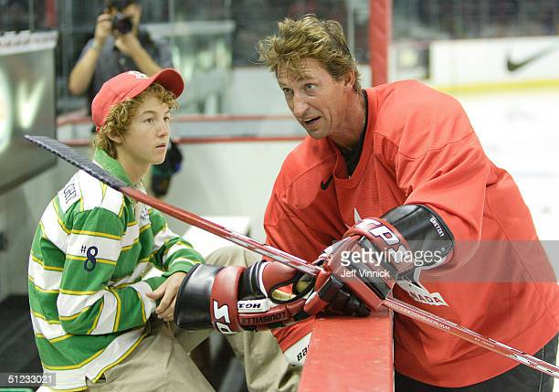 Wayne Gretzky Executive Director of Team Canada talks to his 14 yearold son Ty Gretzky during a Team Canada practice session before Canada's...