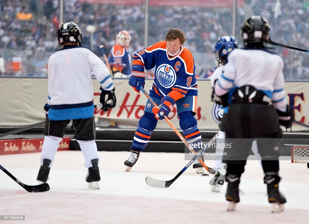 Wayne Gretzky #99 of the Edmonton Oilers alumni plays with kids from the TimBits Hockey Program during the 2016 Tim Hortons NHL Heritage Classic alumni game at Investors Group Field on October 22, 2016 in Winnipeg, Canada.