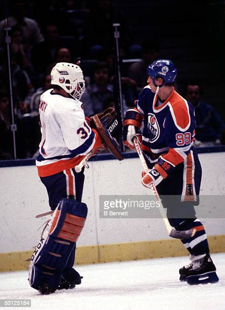 Wayne Gretzky of the Edmonton Oilers bumps into goalie Billy Smith of the New York Islanders during an NHL game circa 1984 at the Nassau Coliseum in...