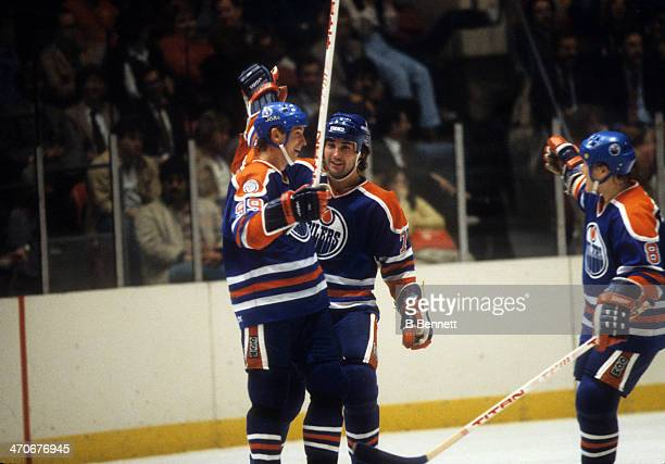Wayne Gretzky of the Edmonton Oilers celebrates a goal with teammates Paul Coffey and Risto Siltanen during an NHL game against the New York Rangers...