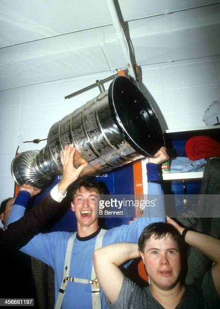 Wayne Gretzky of the Edmonton Oilers celebrates in the locker room with Joey Moss and the Stanley Cup Trophy after the Oilers defeated the...