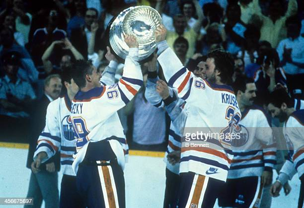 Wayne Gretzky of the Edmonton Oilers hands the Stanley Cup Trophy to Mike Krushelnyski after the Edmonton Oilers defeated the Boston Bruins in Game 5...