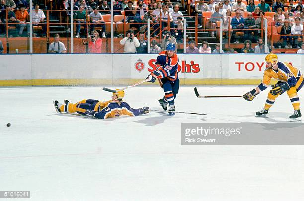 Wayne Gretzky of the Edmonton Oilers makes a pass between defensemen Garry Galley and Jay Wells of the Los Angeles Kings circa March 1988 during a...