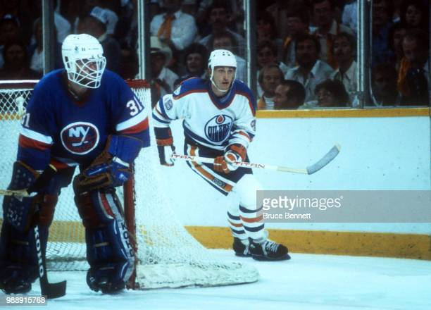 Wayne Gretzky of the Edmonton Oilers skates around the net as goalie Billy Smith of the New York Islanders follows the play during the 1983 Stanley...