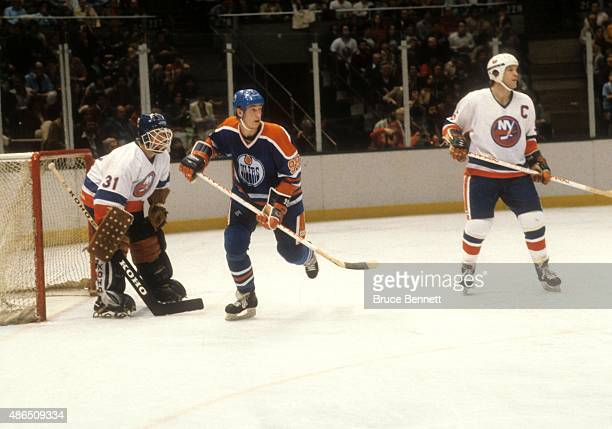 Wayne Gretzky of the Edmonton Oilers skates in front of goalie Billy Smith of the New York Islanders as Denis Potvin of the Islanders defends during...