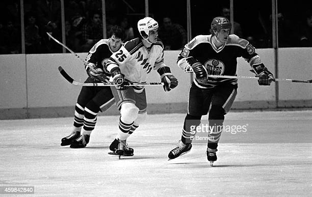 Wayne Gretzky of the Edmonton Oilers skates on the ice as his teammate Blair MacDonald and Mario Marois of the New York Rangers follow behind on...