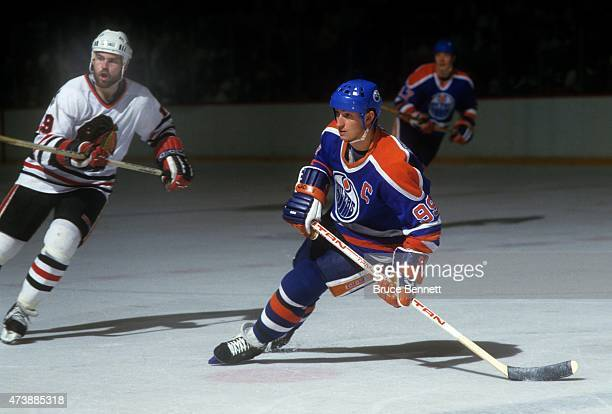 Wayne Gretzky of the Edmonton Oilers skates on the ice as Troy Murray of the Chicago Blackhawks follows behind during the 1985 Western Conference...