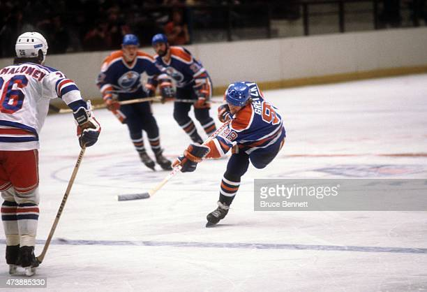 Wayne Gretzky of the Edmonton Oilers takes the shot as Dave Maloney of the New York Rangers goes for the block on November 14 1982 at the Madison...