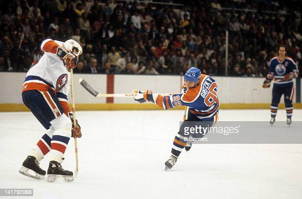 Wayne Gretzky of the Edmonton Oilers takes the shot as Stefan Persson of the New York Islanders defends during the 1983 Stanley Cup Finals in May...