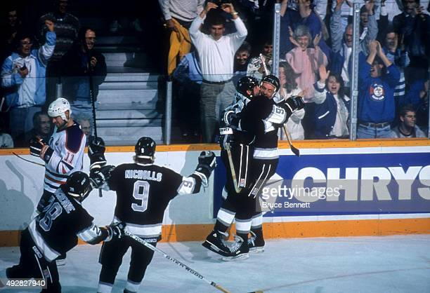 Wayne Gretzky of the Los Angeles Kings is hugged by Larry Robinson after he scored his 1851st career NHL point against the Edmonton Oilers on October...