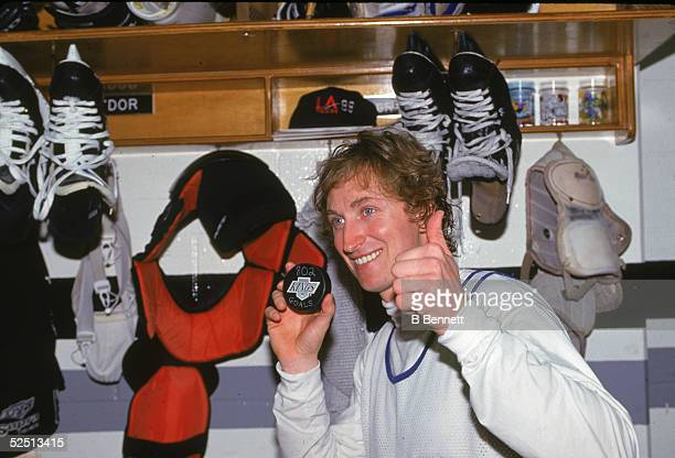 Wayne Gretzky of the Los Angeles Kings poses for a portrait in the locker room while holding up the puck he scored his 802 NHL goal to pass Gordie...