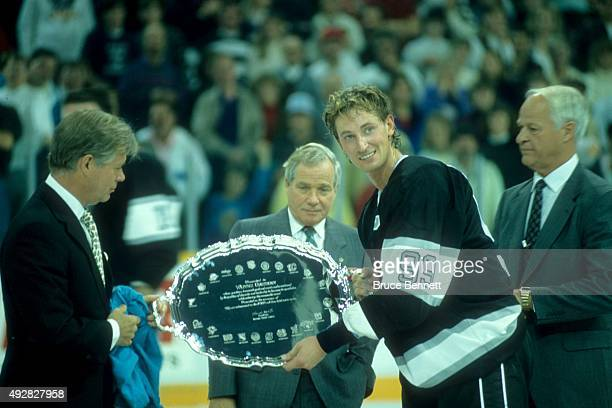 Wayne Gretzky of the Los Angeles Kings receives a silver tea tray from the NHL after he scored his 1851st career NHL point against the Edmonton...