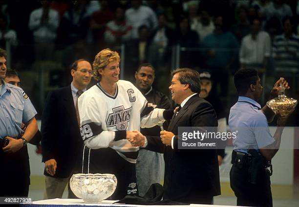 Wayne Gretzky of the Los Angeles Kings shakes hands with owner Bruce McNall during pregame ceremonies after Gretzky scored his 1,851st career NHL...