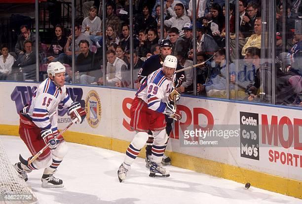 Wayne Gretzky of the New York Rangers checks Josef Beranek of the Edmonton Oilers as John MacLean of the Rangers goes for the puck on October 20 1998...