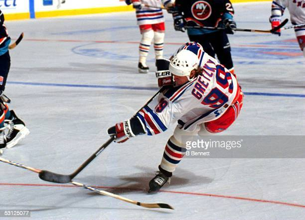 Wayne Gretzky of the New York Rangers shoots the puck during an NHL game against the New York Islanders circa 1997 at the Madison Square Garden in...