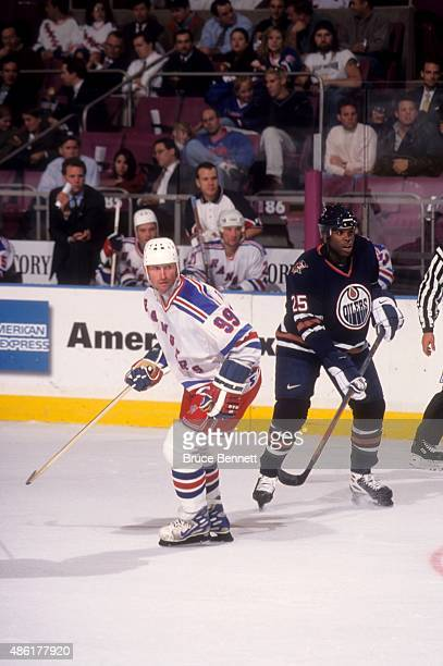 Wayne Gretzky of the New York Rangers skates on the ice as Mike Grier of the Edmonton Oilers follows behind on October 20 1998 at the Madison Square...