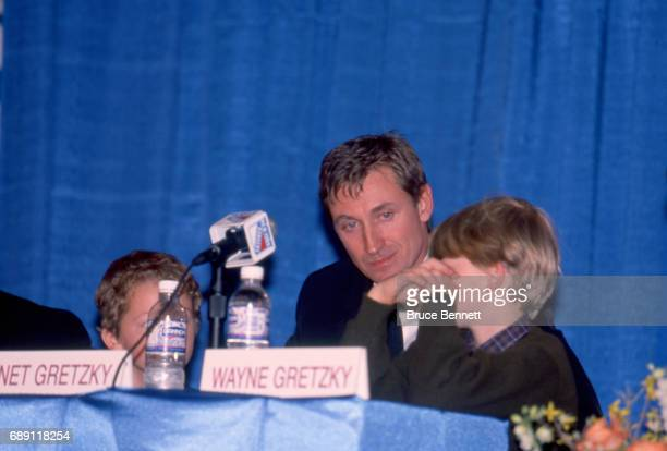 Wayne Gretzky of the New York Rangers with his sons Ty and Trevor talks to the media during the press conference for Gretzky's retirement from the...