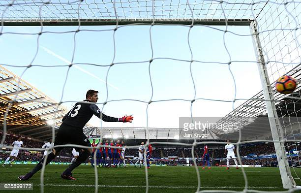 Wayne Hennessey of Crystal Palace watches the ball as Gylfi Sigurdsson of Swansea City scores his team's first goal during the Premier League match...