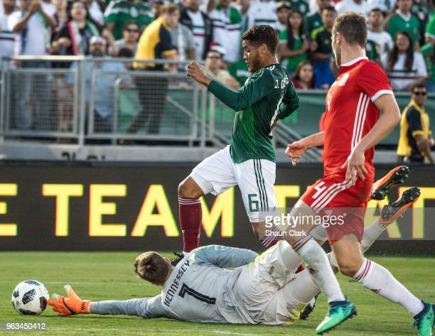 Wayne Hennessey of Wales knocks the ball away from Jonathan Dos Santos of Mexico during the international friendly match between Mexico and Wales at...
