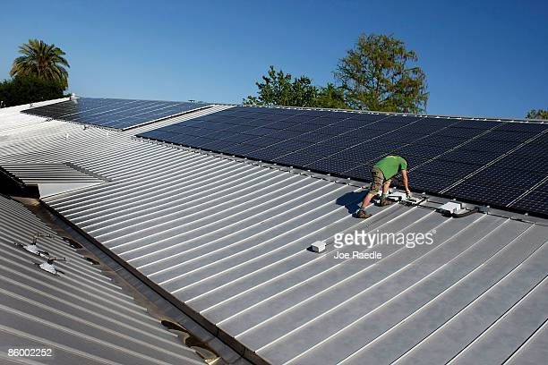 Wayne Irwin, who works for Pure Energy Solar, works on the installation of a solar panel system on the roof of a business on April 15, 2009 in...