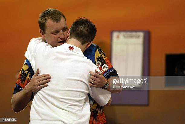 Wayne Mardle consoles Andrew Davies during the Las Vegas Desert Classic II Darts competition at the MGM Grand Hotel and Casino on July 3 2003 in Las...