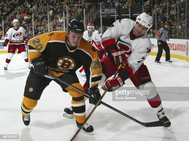 Wayne Primeau of the Boston Bruins and Niclas Wallin of the Carolina Hurricanes battle for the puck on February 5 2006 at the TD Banknorth Garden in...
