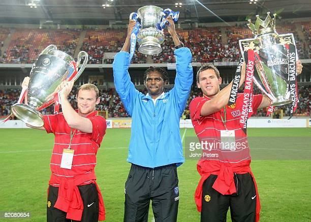 Wayne Rooney and Ben Foster of Manchester United and Kanu of Portsmouth show off the FA Barclays Premiership trophy UEFA Champions League trophy and...