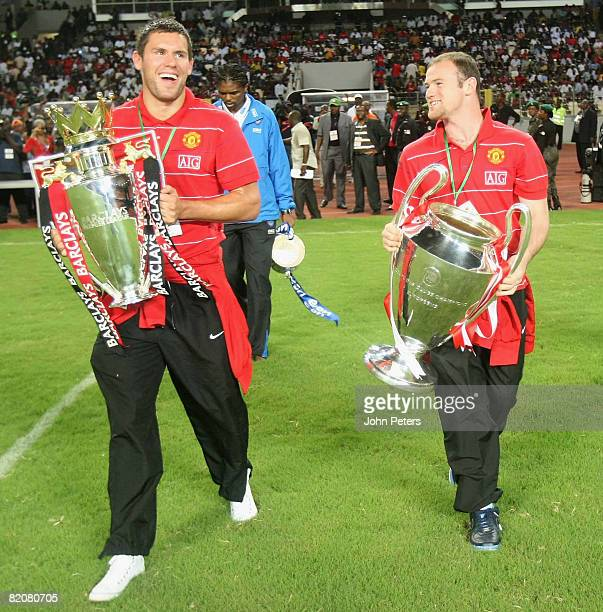 Wayne Rooney and Ben Foster of Manchester United show off the FA Barclays Premiership trophy and UEFA Champions League trophy ahead of the preseason...
