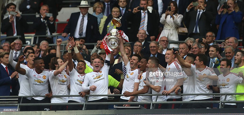 Wayne Rooney and Michael Carrick of Manchester United lift the FA Cup after The Emirates FA Cup final match between Manchester United and Crystal Palace at Wembley Stadium on May 21, 2016 in London, England.