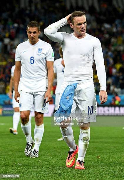 Wayne Rooney and Phil Jagielka of England walk off the pitch after the 2014 FIFA World Cup Brazil Group D match between Uruguay and England at Arena...