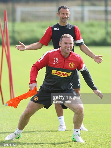 Wayne Rooney and Ryan Giggs of Manchester United in action during a first team training session at Carrington Training Ground on August 24, 2012 in...
