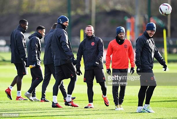 Wayne Rooney and Zlatan Ibrahimovic share a joke during a Manchester United training session on the eve of their UEFA Europa League match against...