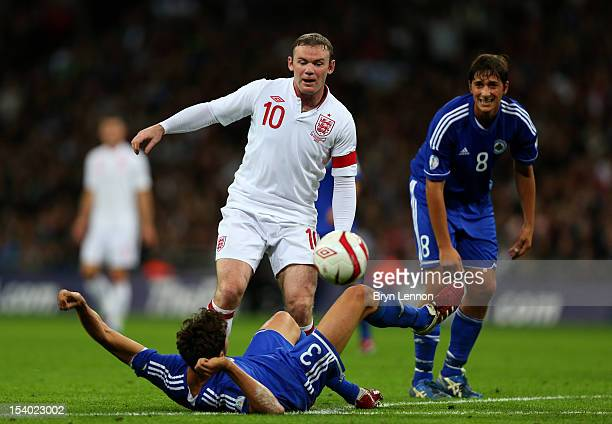 Wayne Rooney captain of England battles for the ball with Mirko Palazzi of San Marino during the FIFA 2014 World Cup Group H qualifying match between...